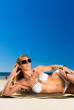 Attractive woman lying in the sun on beach Royalty Free Stock Photos