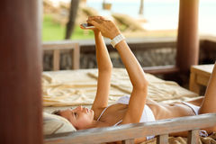 Attractive woman lying on sunbed and making selfie Stock Photos