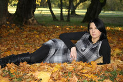 Attractive woman lying on yellow leafage. Attractive woman in park lying on yellow leafage Stock Image