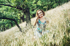 Attractive woman makes heart shape with her hands in the forest Royalty Free Stock Photography