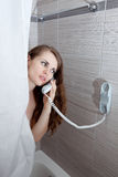 Attractive woman making call in bathroom. Gorgeous woman behind curtain making a call at modern bathroom stock photos