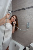Attractive woman making call in bathroom. Gorgeous woman behind curtain making a call at modern bathroom royalty free stock image