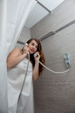 Attractive woman making call in bathroom. Gorgeous woman behind curtain making a call at modern bathroom stock photo