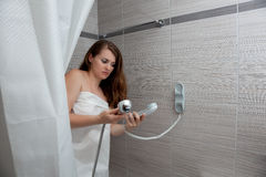Attractive woman making call in bathroom. Gorgeous woman behind curtain making a call at modern bathroom stock images