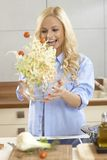 Attractive woman making salad in kitchen Stock Photo