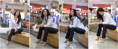 Attractive woman with male white shirt and trousers posing in mall. Beautiful fashionable young girl sitting on bench. In modern shopping center. Long hair Stock Photo