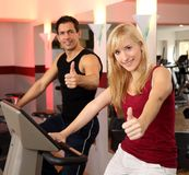 Attractive woman and a man cycling in a gym. A handsome men and an attractive women working out on a bicycle in a fitness center Stock Photos