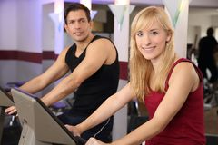 Attractive woman and a man cycling in a gym. A handsome men and an attractive women working out on a bicycle in a fitness center Royalty Free Stock Photo