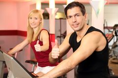 Attractive woman and a man cycling in a gym. A handsome men and an attractive women working out on a bicycle in a fitness center showing thumbs it Royalty Free Stock Photography