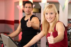 Attractive woman and a man cycling in a gym. A handsome men and an attractive women working out on a bicycle in a fitness center showing thumbs up Royalty Free Stock Images