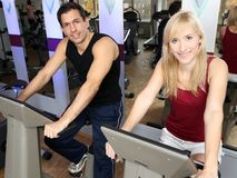 Attractive woman and a man cycling in a gym. A handsome men and an attractive women working out on a bicycle in a fitness center Stock Photo