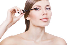 Attractive woman and mascara brush. On white background Stock Images