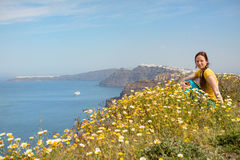 Attractive woman on the meadow full of flowers on Santorini island Stock Photography