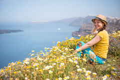 Attractive woman on the meadow full of flowers on Santorini island Royalty Free Stock Images