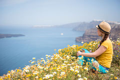 Attractive woman on the meadow full of flowers on Santorini island Royalty Free Stock Image