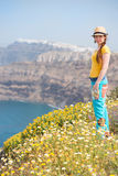 Attractive woman on the meadow full of flowers on Santorini island Stock Images