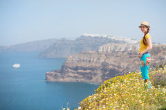 Attractive woman on the meadow full of flowers on Santorini island Royalty Free Stock Photo
