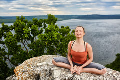 Attractive woman meditating in lotus posture sitting on the rock above river. Royalty Free Stock Image