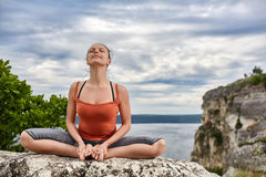 Attractive woman meditating in lotus posture sitting on the rock above river. Stock Photo
