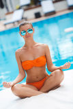 Attractive woman meditating by the pool. royalty free stock photo