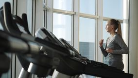 Attractive woman of middle age is running on tread mill in sport gym