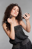 Attractive woman with morror and brush Royalty Free Stock Photo