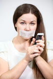 Attractive woman with mouth sealed can not talk on cell phone, grey background Royalty Free Stock Images