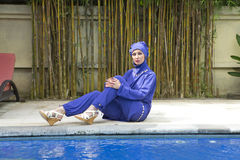 Attractive woman in a Muslim swimwear burkini  on a pool side in a tropical garden Royalty Free Stock Photos