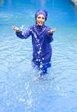 Attractive woman in a Muslim swimwear burkini splashes water in the pool.  Royalty Free Stock Photo