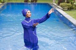 Attractive woman in a Muslim swimwear burkini splashes water in the pool.  Royalty Free Stock Image