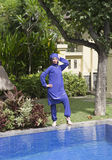 Attractive woman in a Muslim swimwear burkini stand on a pool side in a tropical garden Stock Photo