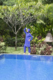 Attractive woman in a Muslim swimwear burkini stand on a pool side in a tropical garden Royalty Free Stock Photography