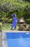 Attractive woman in a Muslim swimwear burkini stand on a pool side in a tropical garden Royalty Free Stock Photo