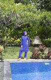 Attractive woman in a Muslim swimwear burkini stand on a pool side in a tropical garden Royalty Free Stock Photos