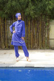Attractive woman in a Muslim swimwear burkini stand on a pool side in a tropical garden Royalty Free Stock Images