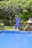 Attractive woman in a Muslim swimwear burkini stand on a pool side in a tropical garden Stock Photography