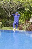Attractive woman in a Muslim swimwear burkini stand on a pool side in a tropical garden.  Stock Images