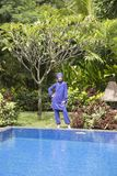 Attractive woman in a Muslim swimwear burkini stand on a pool side in a tropical garden.  Royalty Free Stock Photography