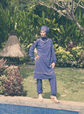 Attractive woman in a Muslim swimwear burkini stand on a pool side in a tropical garden, Royalty Free Stock Image