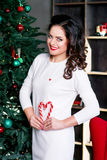 Attractive woman nearly christmas tree Royalty Free Stock Image
