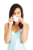 Attractive woman in nightwear drinking from cup Royalty Free Stock Photo