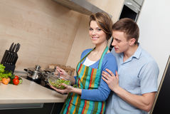 Attractive woman offers her husband to taste salad Royalty Free Stock Photos