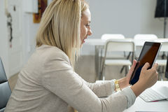 Attractive woman in the office. Tablet, electronics. Royalty Free Stock Photo