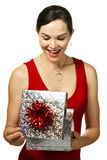 Attractive woman opening gift box. Very attractive young woman smiling and opening and looking in to a gift box. Isolated on white Royalty Free Stock Photo
