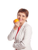 Attractive woman 50 with orange in hand Stock Photos
