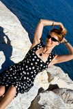 Attractive woman with outstretched arms outdoors. Attractive woman with outstretched arms sitting on the Gaeta sea coast at sunny day Royalty Free Stock Photos