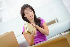 Attractive woman packing books in cardboard box. Attractive woman is packing books in cardboard box Royalty Free Stock Photography