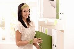 Attractive woman packing folders on shelf Royalty Free Stock Photography
