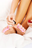 Attractive woman painting her toes. Royalty Free Stock Photography