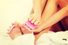 Attractive woman painting her toes in bed Stock Images